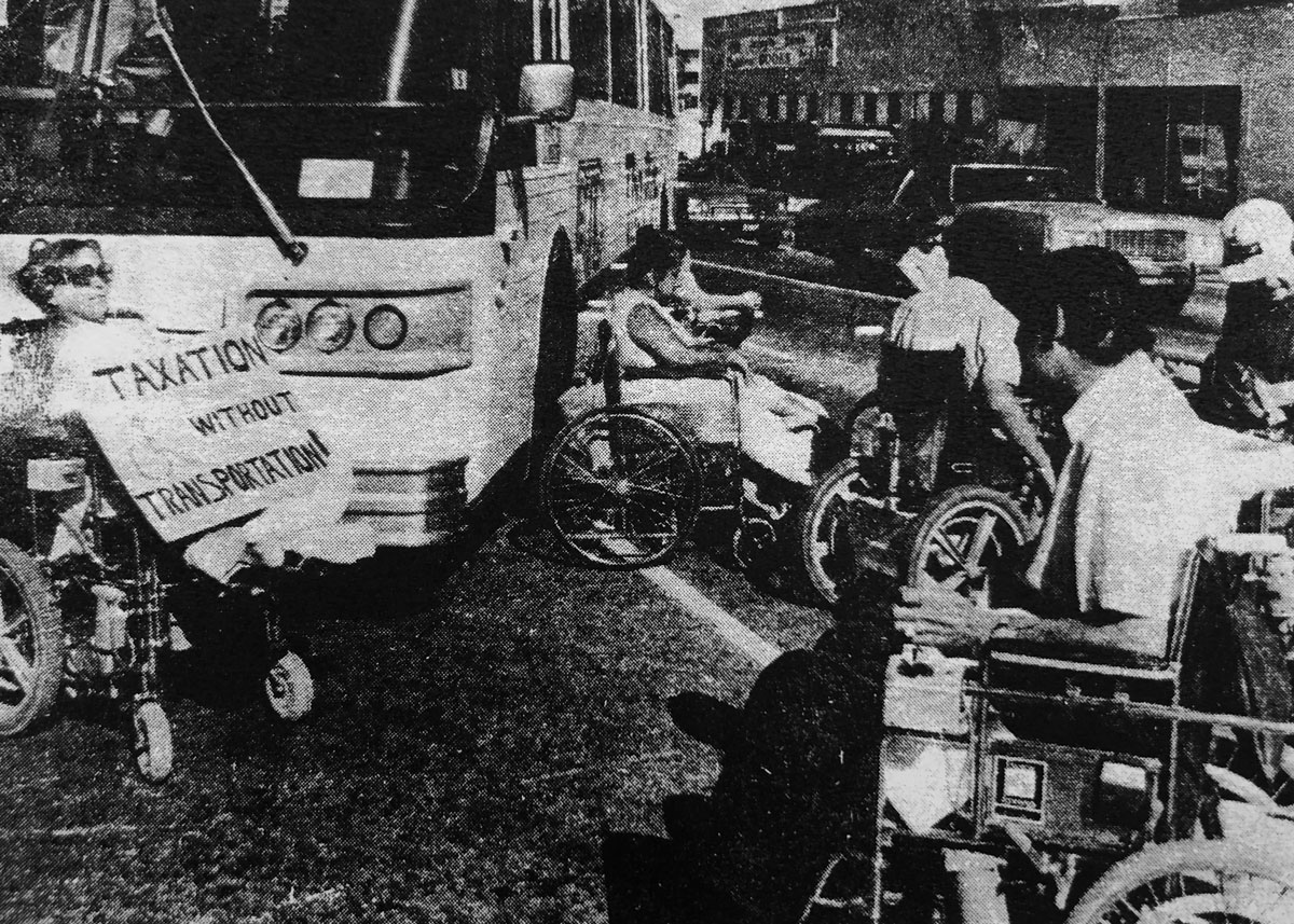 The 'Gang of 19', part of the Atlantis activist group, lies down in front of buses and barricades themselves around two buses at Colfax Ave. and Broadway Ave. July 5-6, 1978