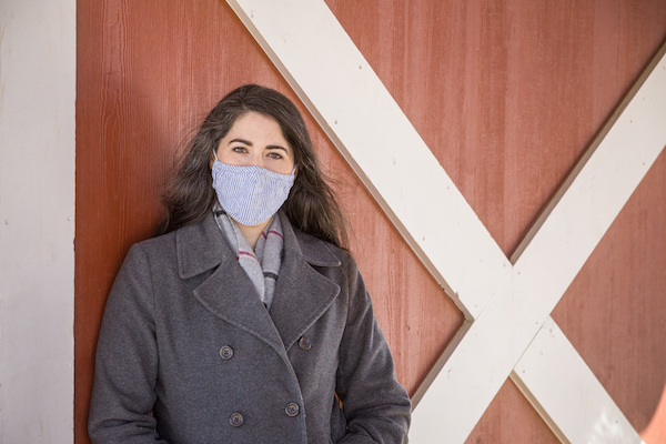 Amelia thompson wearing a mask in front of a barn