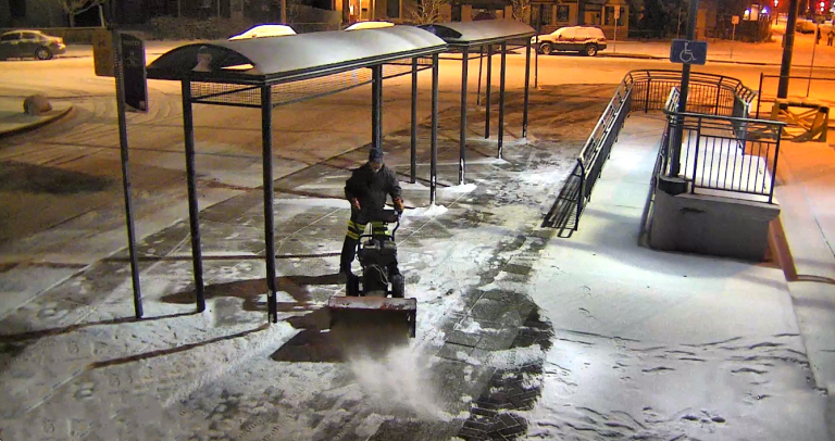 Employee removing snow on the sidewalk at 30th & Downing Station