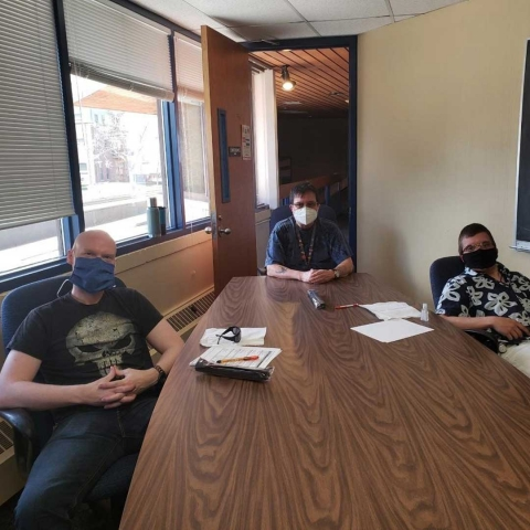 Three gentlemen in a conference room wearing face masks