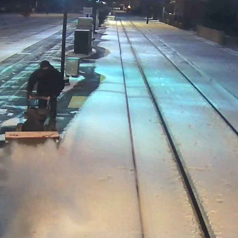 Shoveling the snow off the sidewalk at a light rail station